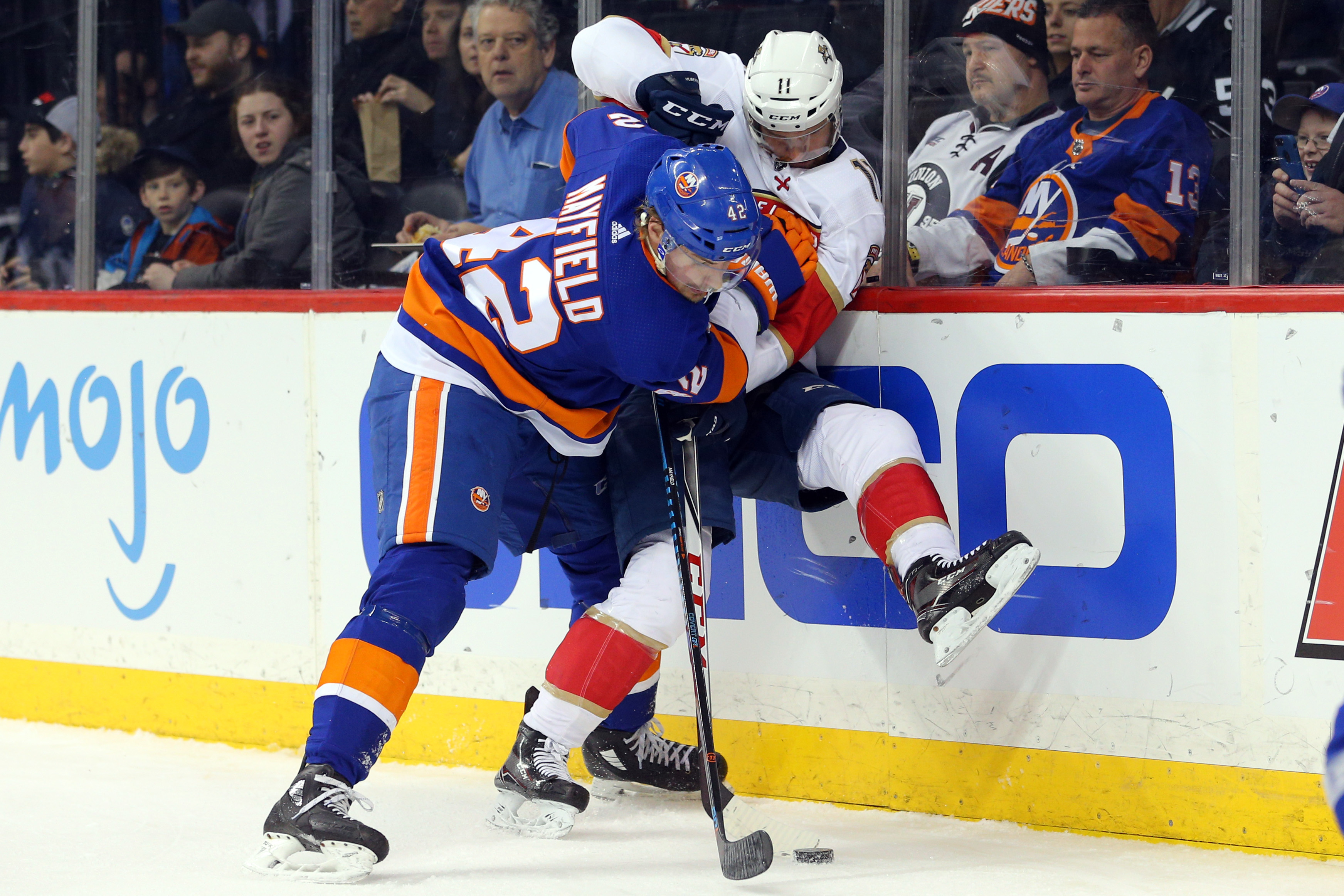 Jan 30, 2018; Brooklyn, NY, USA; New York Islanders defenseman Scott Mayfield (42) hits Florida Panthers center Jonathan Huberdeau (11) as they fight for the puck during the first period at Barclays Center. Mandatory Credit: Brad Penner-USA TODAY Sports
