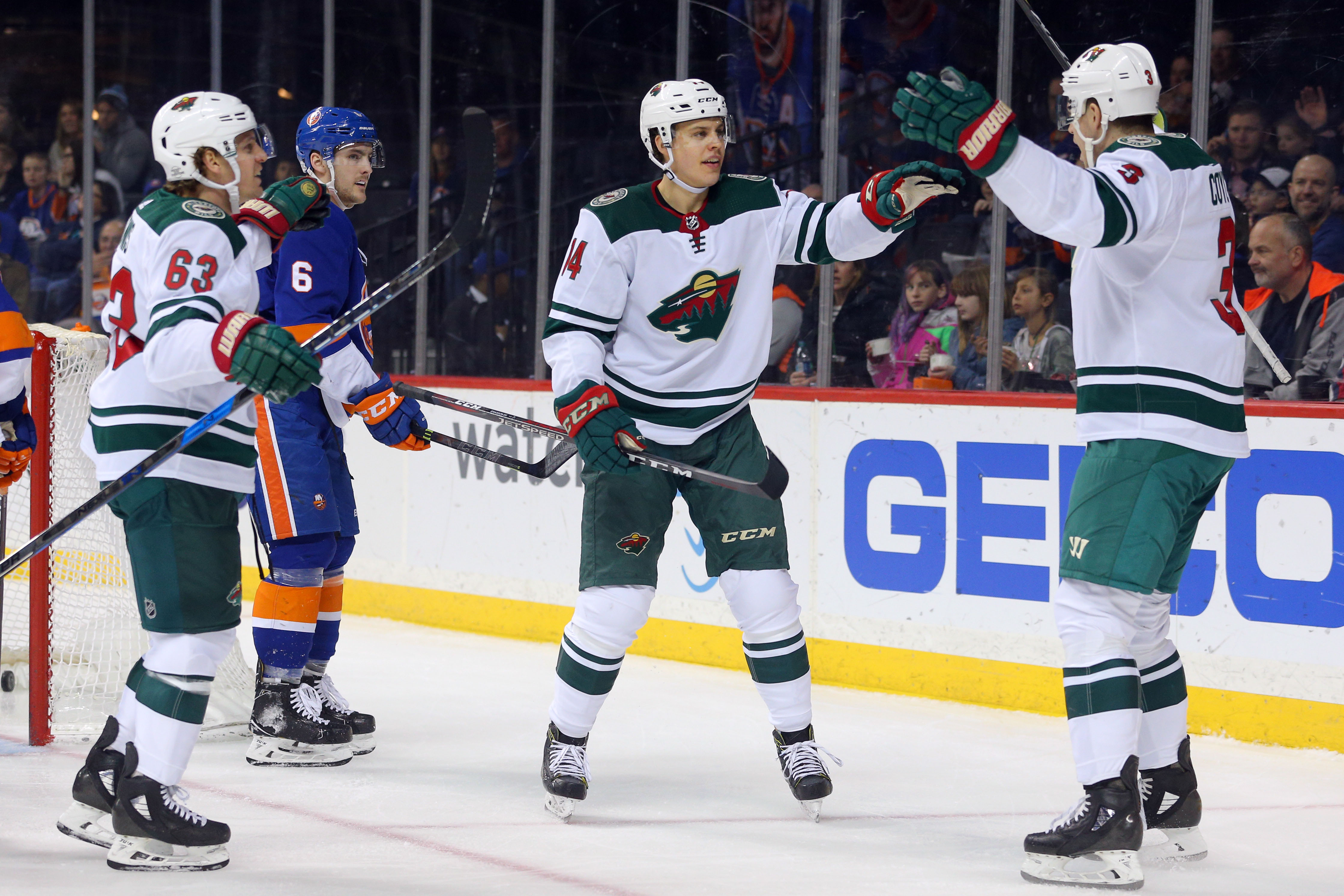 Feb 19, 2018; Brooklyn, NY, USA; Minnesota Wild center Joel Eriksson Ek (14) celebrates his goal against the New York Islanders with center Charlie Coyle (3) and left wing Tyler Ennis (63) during the first period at Barclays Center. Mandatory Credit: Brad Penner-USA TODAY Sports