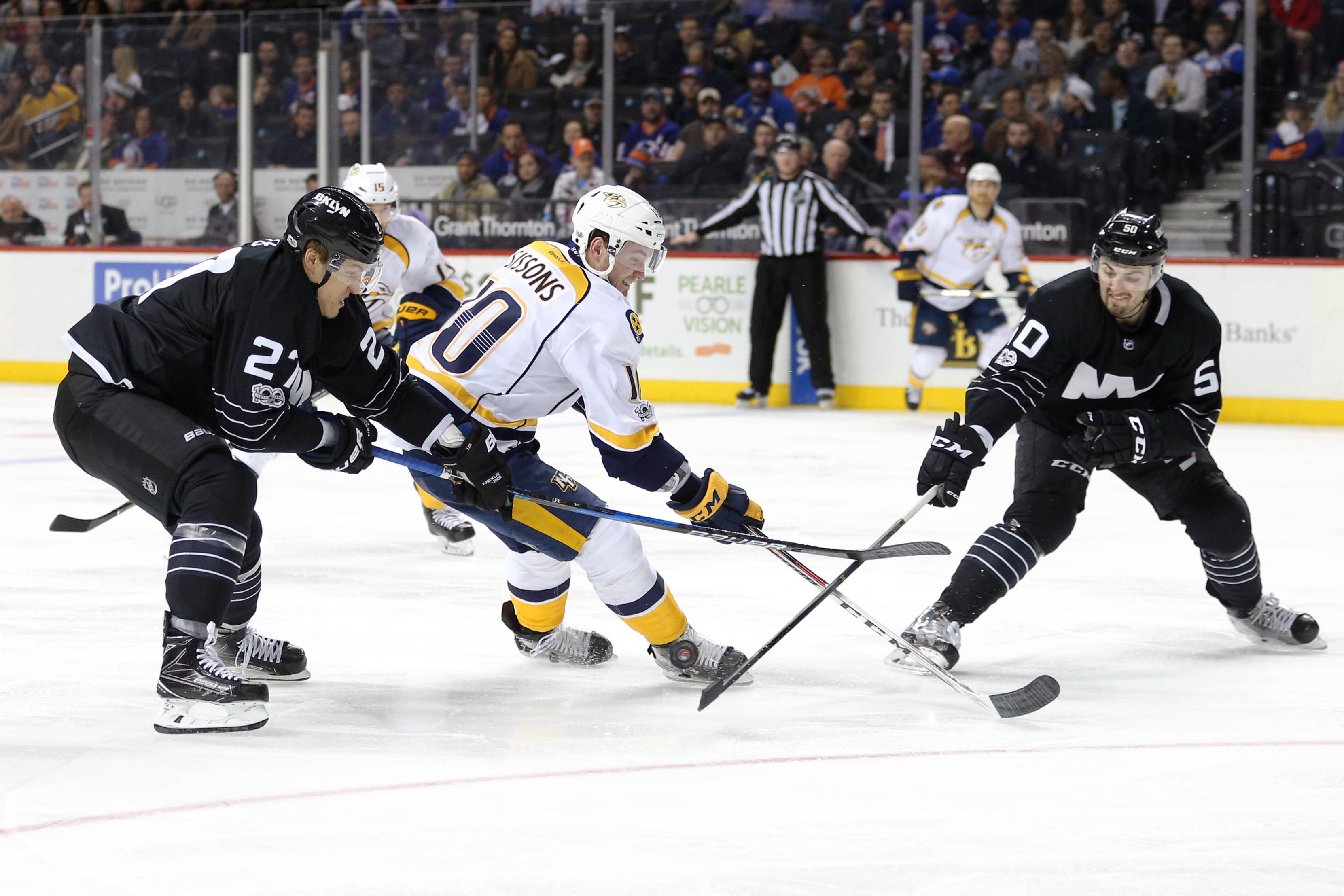 Mar 27, 2017; Brooklyn, NY, USA; Nashville Predators center Colton Sissons (10) plays the puck against New York Islanders center Anders Lee (27) and New York Islanders defenseman Adam Pelech (50) during the third period at Barclays Center. Mandatory Credit: Brad Penner-USA TODAY Sports