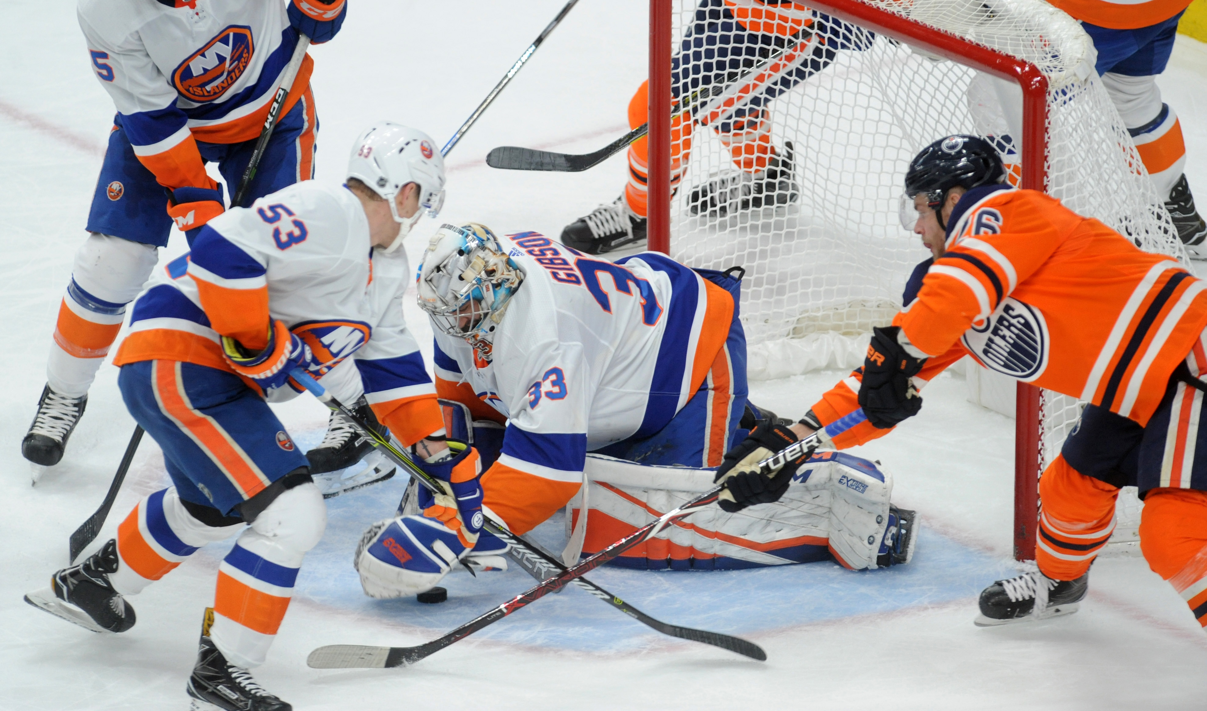 Mar 8, 2018; Edmonton, Alberta, CAN; New York Islanders goalie Christopher Gibson (33) battles for the puck with Islanders center Casey Cizikas (53) and Islanders defenceman Johnny Boychuck (55) helps as Edmonton Oilers right winger Iiro Pakarinen (26) skates towards them during the first period at Rogers Place. Mandatory Credit: Walter Tychnowicz-USA TODAY Sports