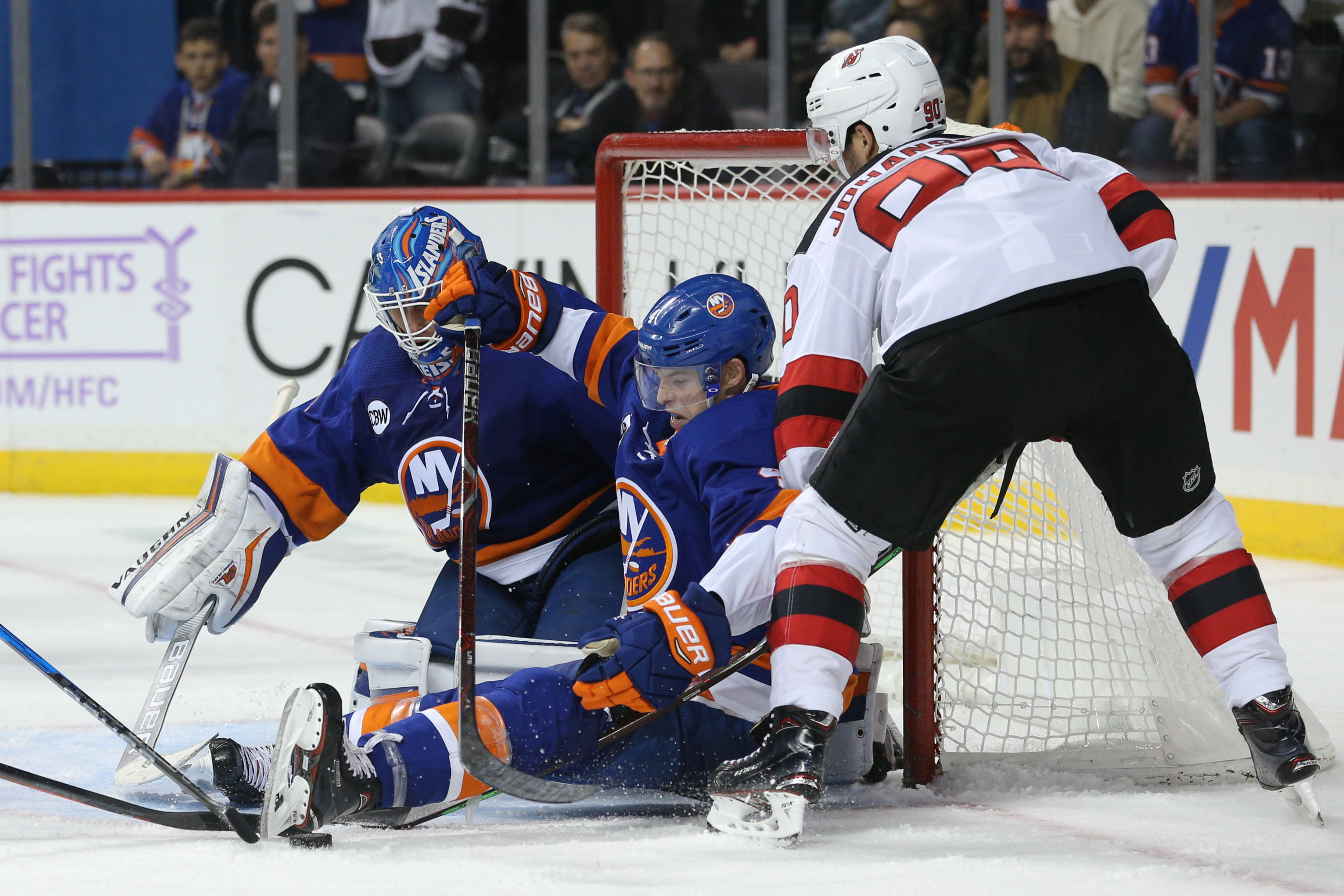 Nov 3, 2018; Brooklyn, NY, USA; New York Islanders goaltender Thomas Greiss (1) makes a save against New Jersey Devils left wing Marcus Johansson (90) in front of Islanders defenseman Thomas Hickey (4) during the third period at Barclays Center. Mandatory Credit: Brad Penner-USA TODAY Sports
