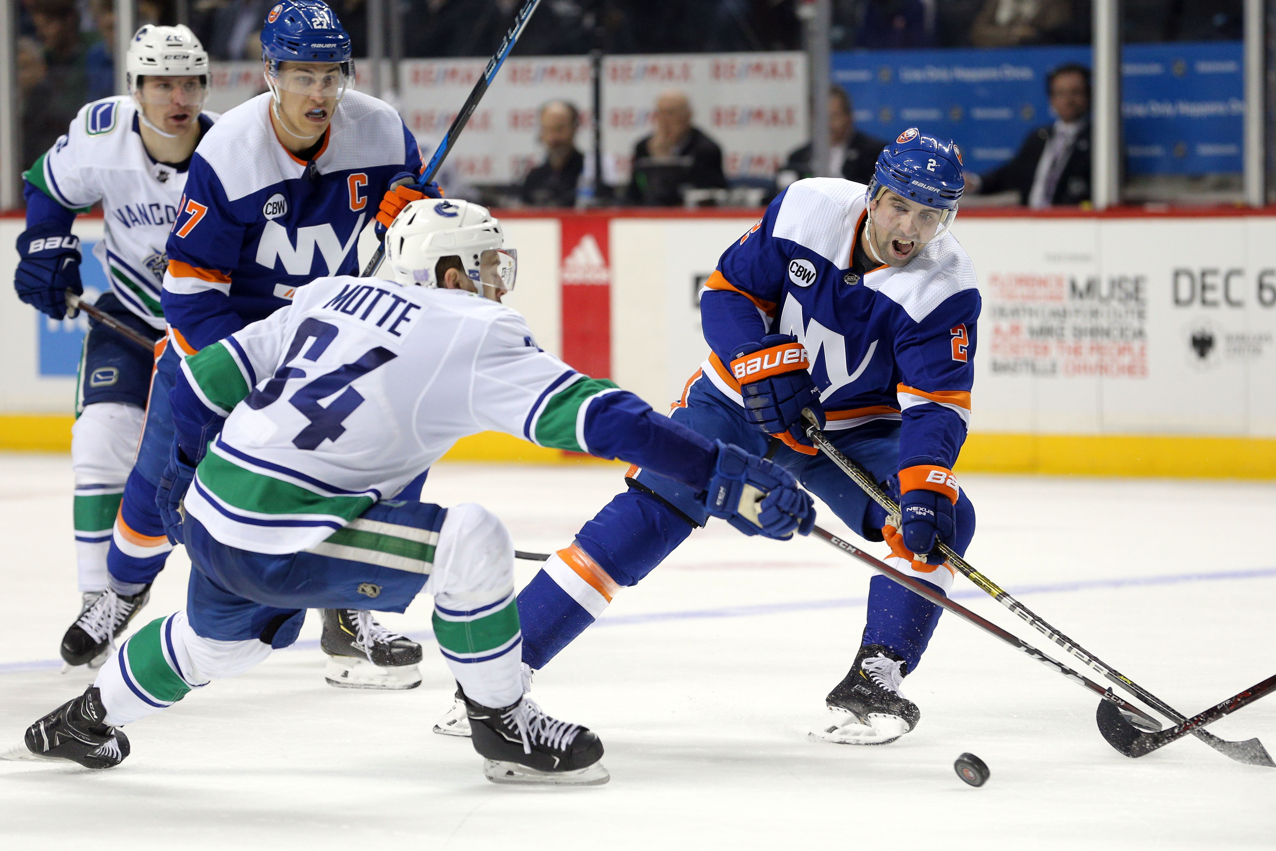 Nov 13, 2018; Brooklyn, NY, USA; New York Islanders defenseman Nick Leddy (2) plays the puck against Vancouver Canucks center Tyler Motte (64) during the second period at Barclays Center. Mandatory Credit: Brad Penner-USA TODAY Sports