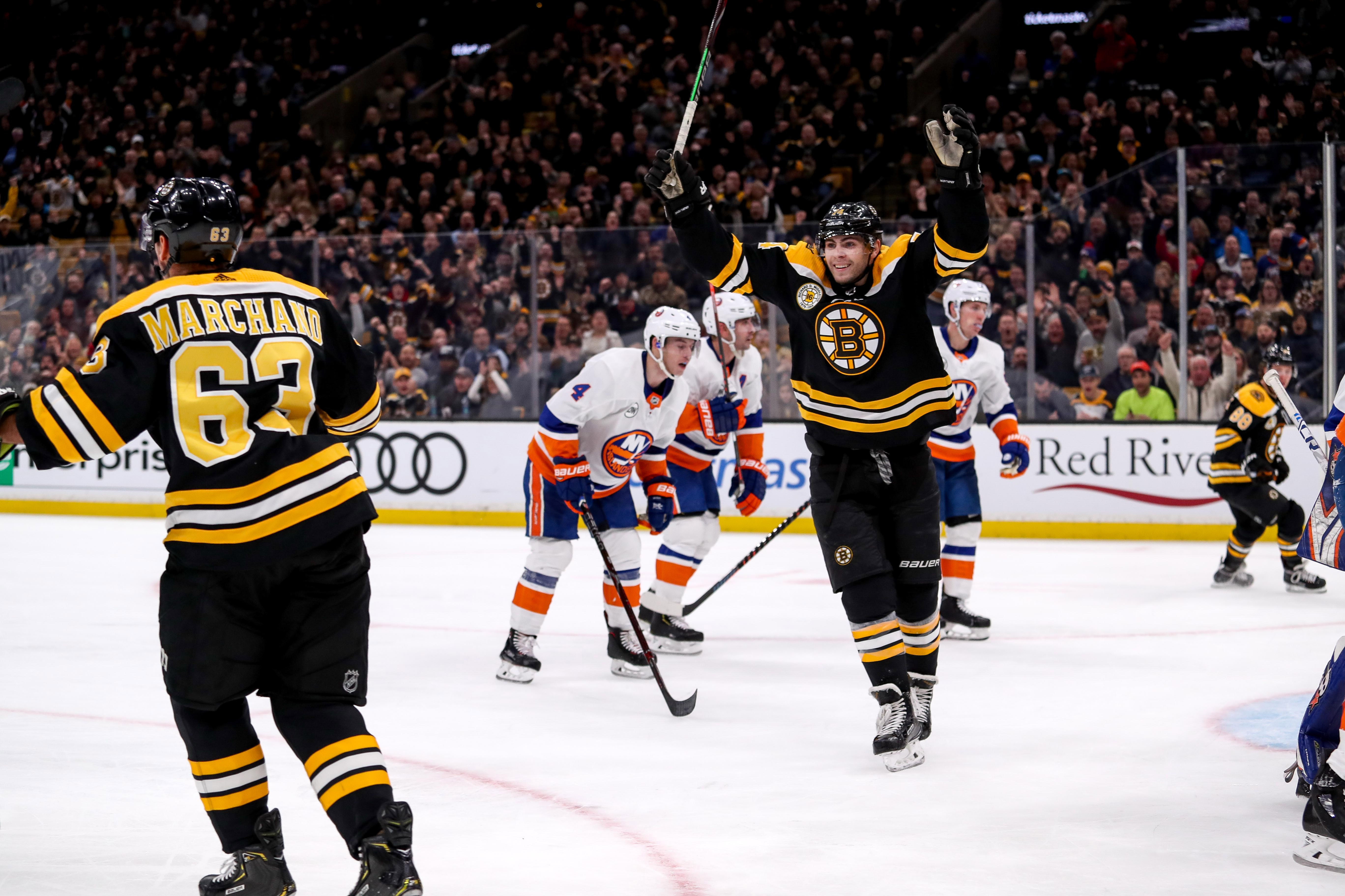 Nov 29, 2018; Boston, MA, USA; Boston Bruins left wing Jake DeBrusk (74) celebrates after a goal by Boston left wing Brad Marchand (63) against the New York Islanders during the second period at TD Garden. Mandatory Credit: Paul Rutherford-USA TODAY Sports