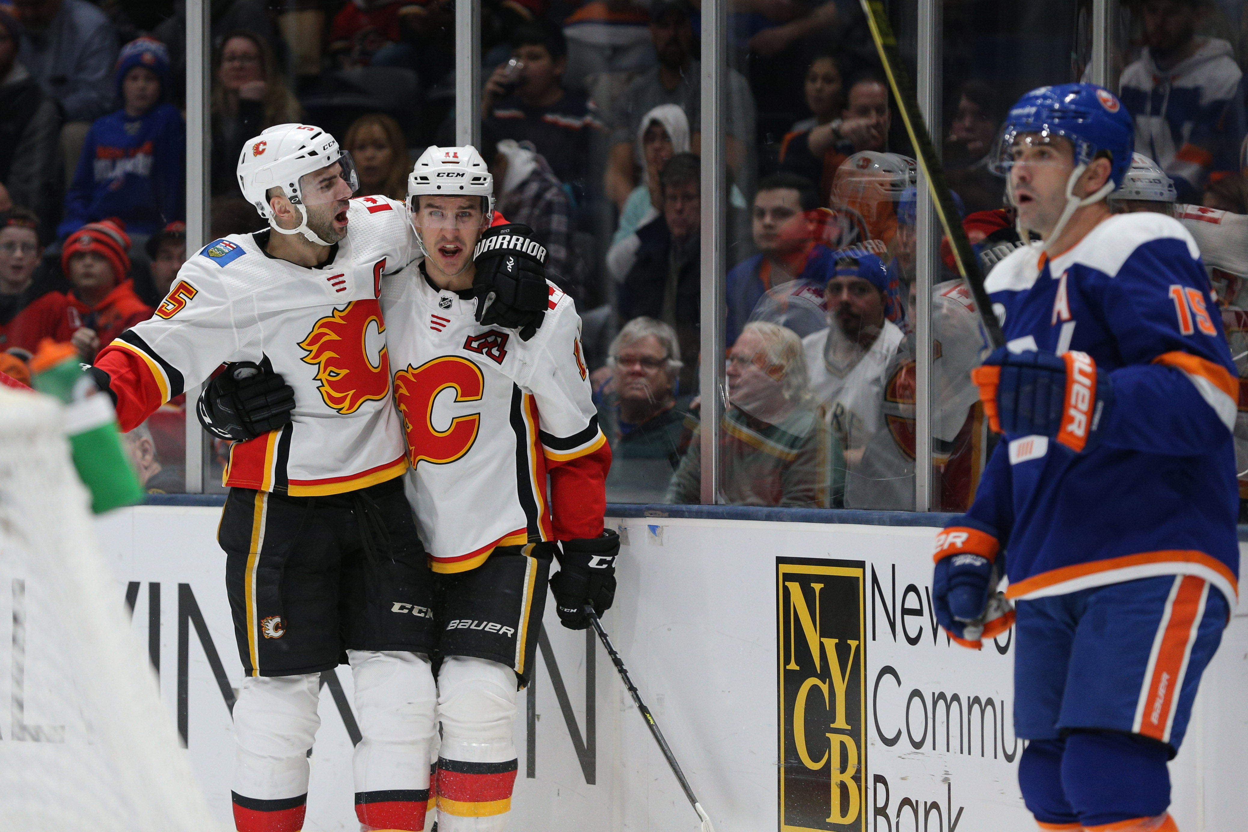 Feb 26, 2019; Uniondale, NY, USA; Calgary Flames center Mikael Backlund (11) celebrates with Calgary Flames defenseman Mark Giordano (5) in front of New York Islanders right wing Cal Clutterbuck (15) after scoring a goal during the third period at Nassau Veterans Memorial Coliseum. Mandatory Credit: Brad Penner-USA TODAY Sports