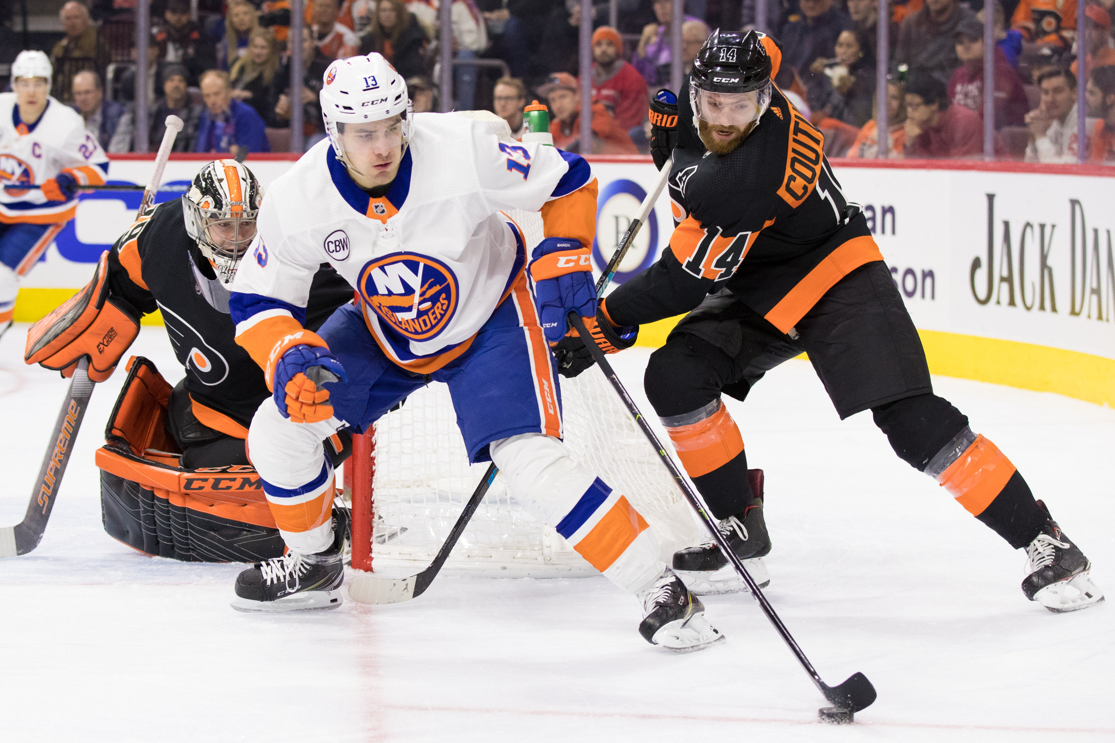 Mar 23, 2019; Philadelphia, PA, USA; New York Islanders center Mathew Barzal (13) skates with the puck in front of Philadelphia Flyers center Sean Couturier (14) and goaltender Carter Hart (79) during the second period at Wells Fargo Center. Mandatory Credit: Bill Streicher-USA TODAY Sports