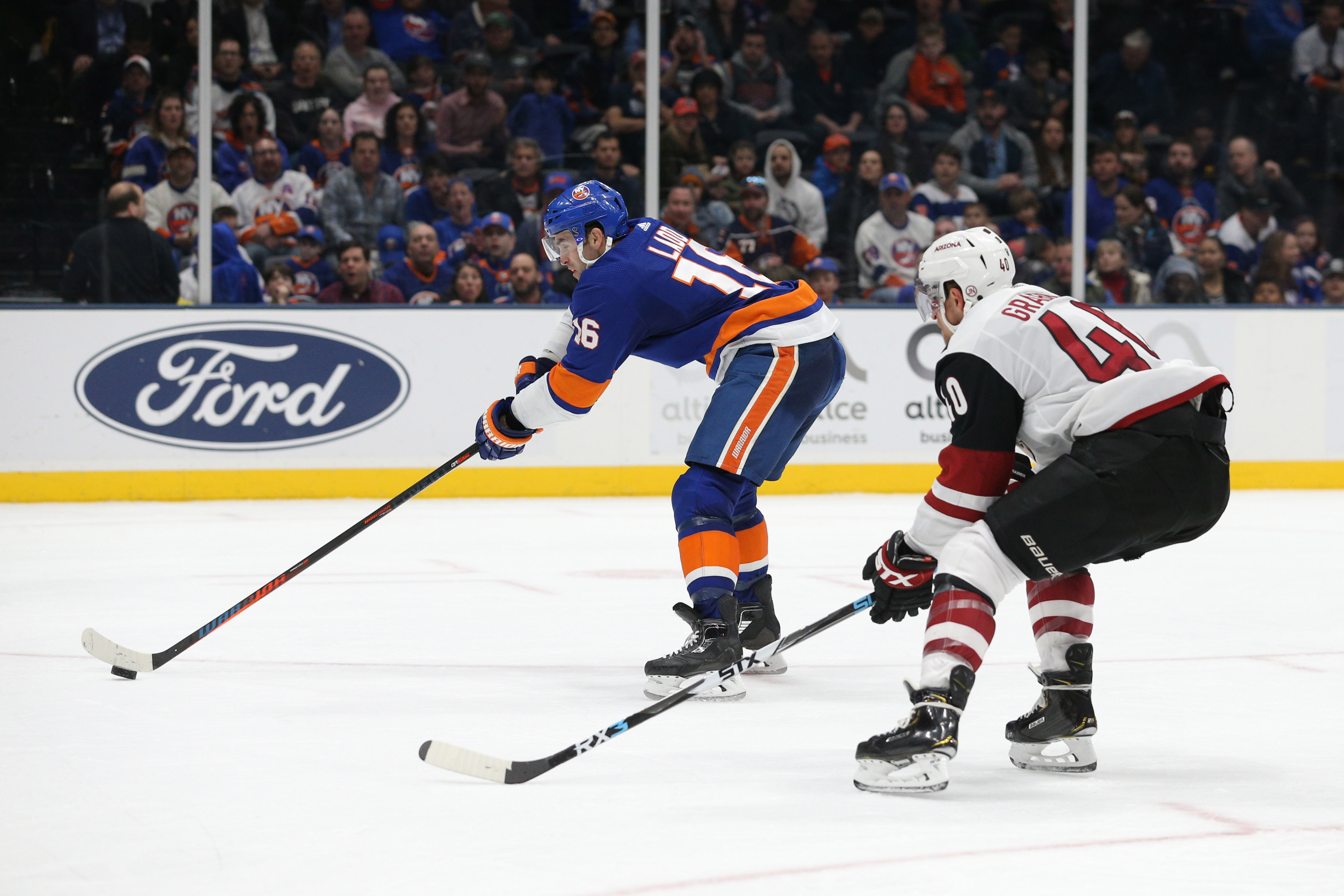 Mar 24, 2019; Uniondale, NY, USA; New York Islanders left wing Andrew Ladd (16) takes a backhanded shot in front of Arizona Coyotes right wing Michael Grabner (40) during the second period at Nassau Veterans Memorial Coliseum. Mandatory Credit: Brad Penner-USA TODAY Sports