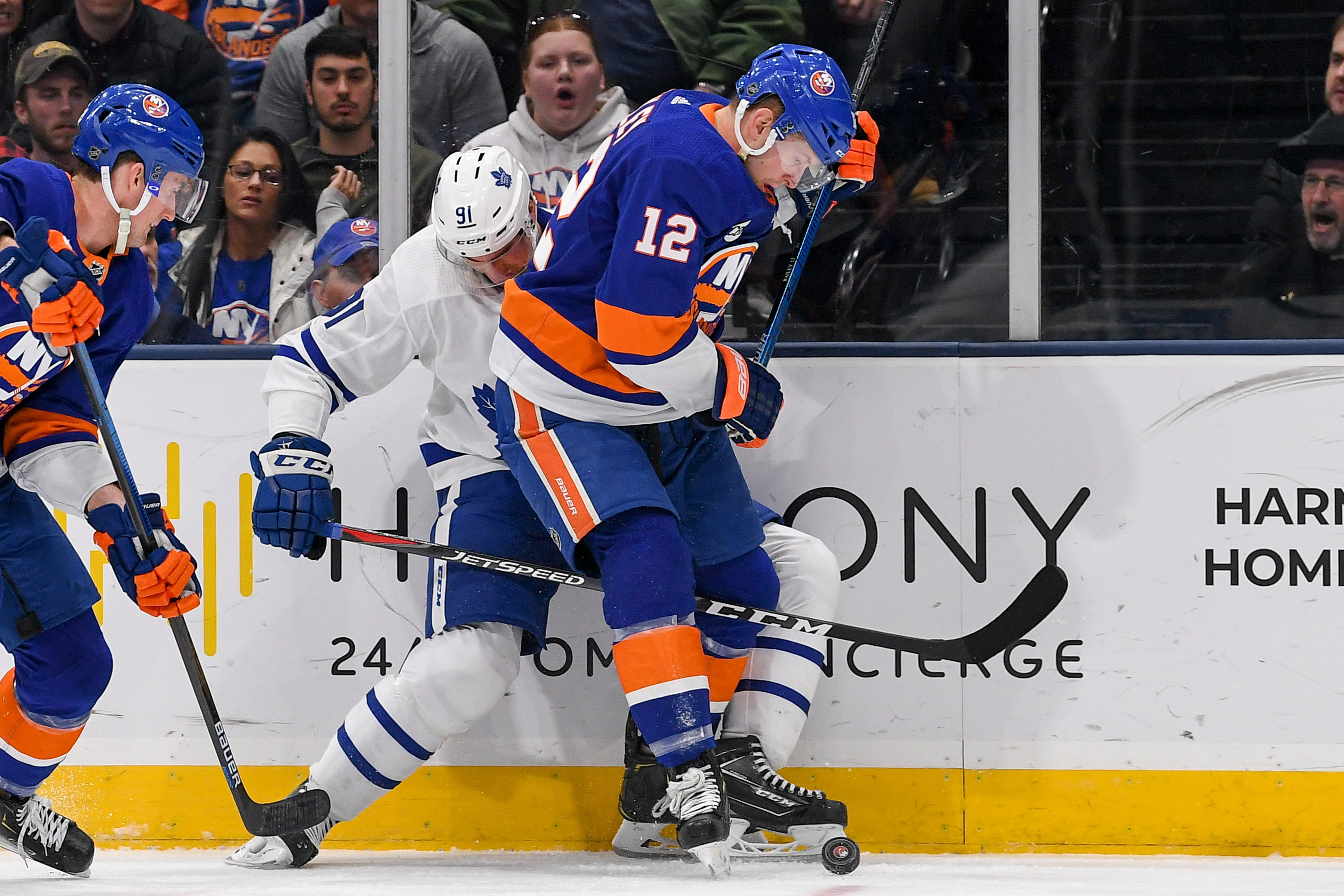 Apr 1, 2019; Uniondale, NY, USA; Toronto Maple Leafs center John Tavares (91) and New York Islanders right wing Josh Bailey (12) battle for the puck on the boards during the second period at Nassau Veterans Memorial Coliseum. Mandatory Credit: Dennis Schneidler-USA TODAY Sports