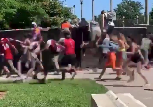 Watch: Massive crowd of people storm the gates at Lollapalooza, leap over wall