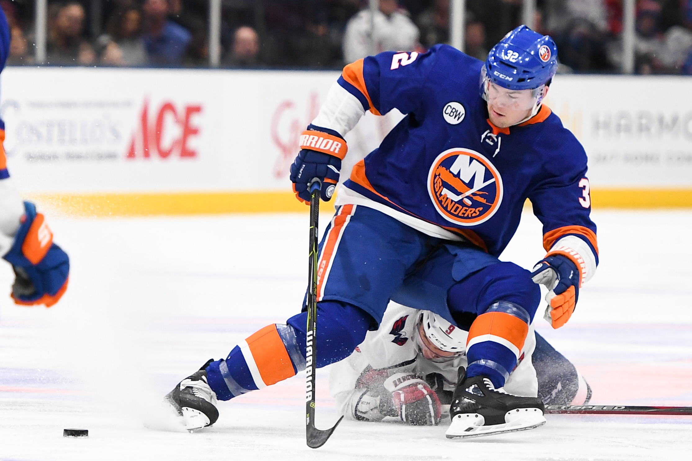 Mar 1, 2019; Uniondale, NY, USA; Washington Capitals defenseman Dmitry Orlov (9) and New York Islanders left wing Ross Johnston (32) battle for the puck during the third period at Nassau Veterans Memorial Coliseum. Mandatory Credit: Dennis Schneidler-USA TODAY Sports