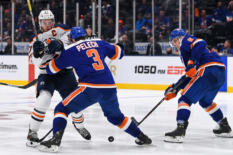 Oct 8, 2019; Uniondale, NY, USA; New York Islanders defenseman Adam Pelech (3) pushes Edmonton Oilers center Connor McDavid (97) off the puck during the third period at Nassau Veterans Memorial Coliseum. Mandatory Credit: Dennis Schneidler-USA TODAY Sports