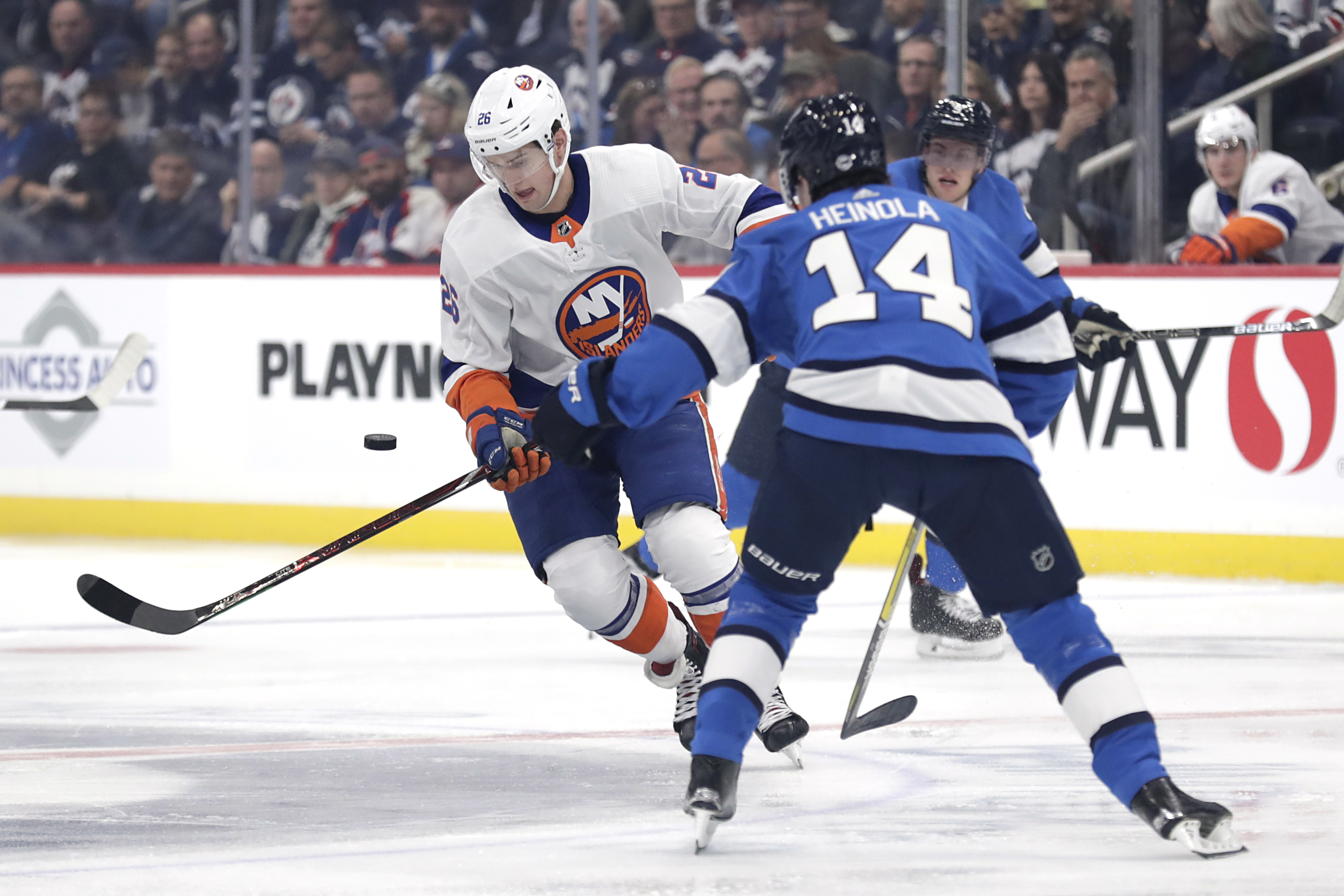 Oct 17, 2019; Winnipeg, Manitoba, CAN; New York Islanders right wing Oliver Wahlstrom (26) tries to control the puck from Winnipeg Jets defenseman Ville Heinola (14) in the first period at Bell MTS Place. Mandatory Credit: James Carey Lauder-USA TODAY Sports