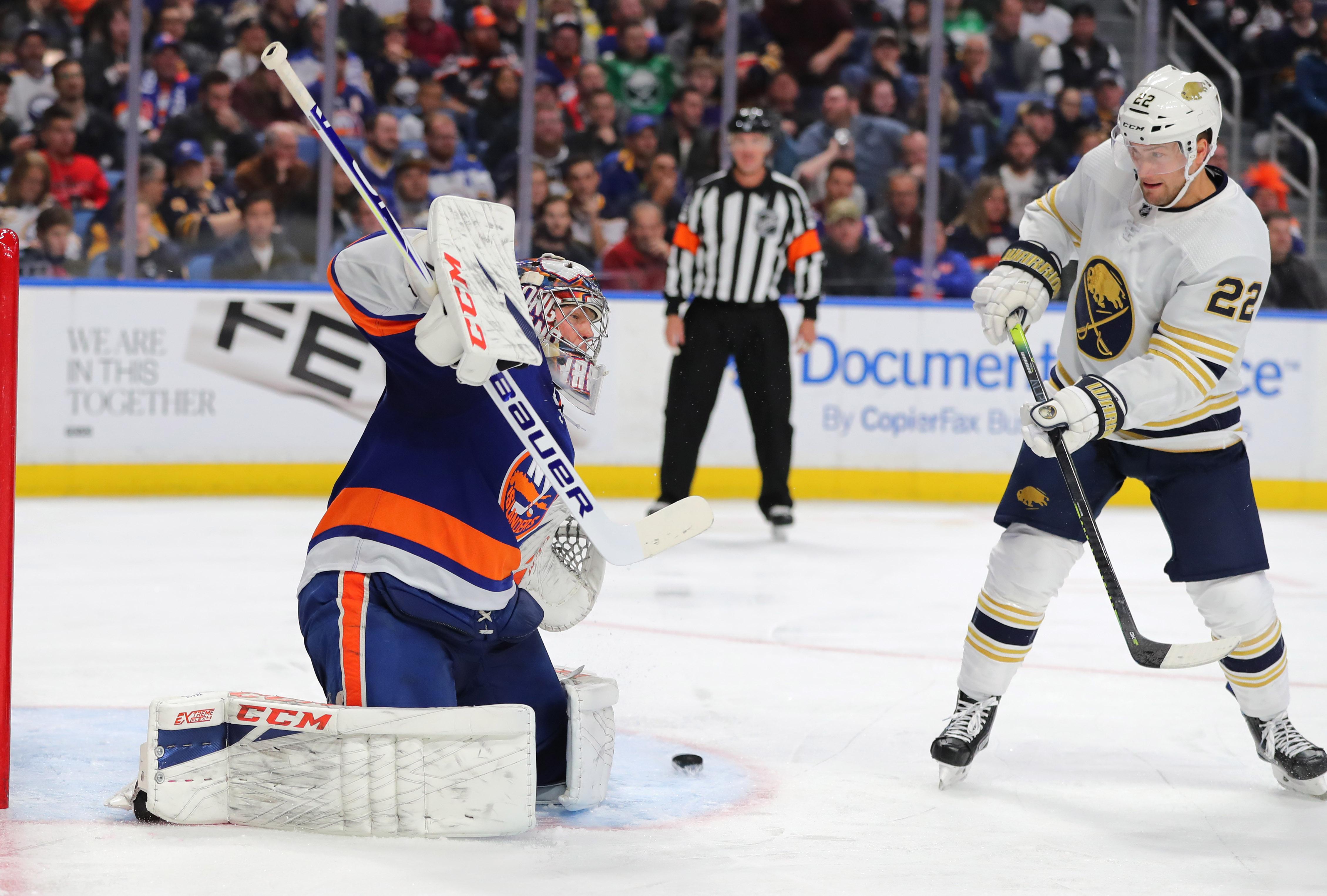 Nov 2, 2019; Buffalo, NY, USA; Buffalo Sabres left wing Johan Larsson (22) deflects a shot on New York Islanders goaltender Semyon Varlamov (40) during the second period at KeyBank Center. Mandatory Credit: Timothy T. Ludwig-USA TODAY Sports