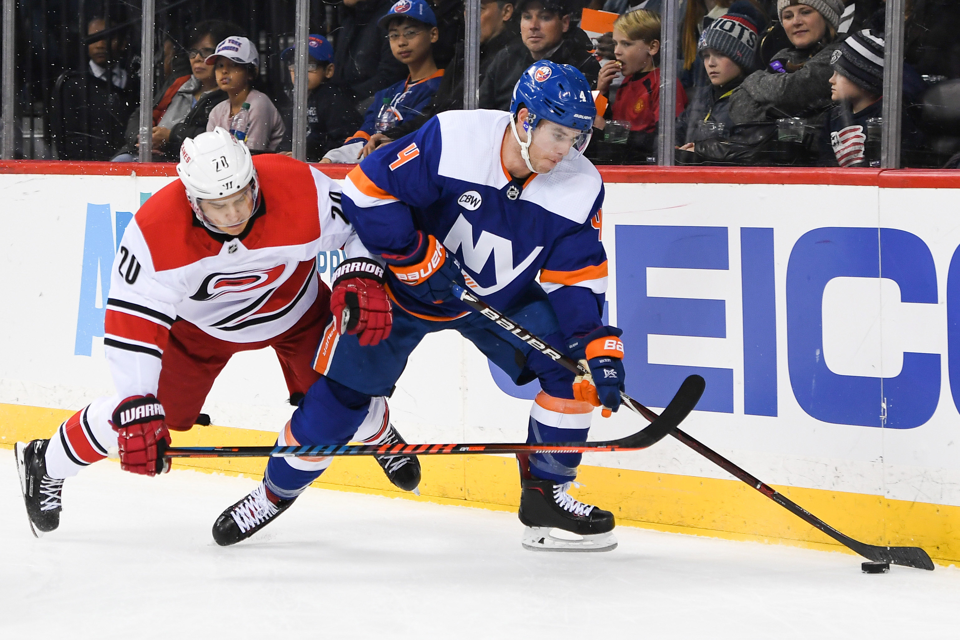 Nov 24, 2018; Brooklyn, NY, USA; New York Islanders defenseman Thomas Hickey (4) and Carolina Hurricanes center Sebastian Aho (20) battle for the puck behind the goal during the first period at Barclays Center. Mandatory Credit: Dennis Schneidler-USA TODAY Sports