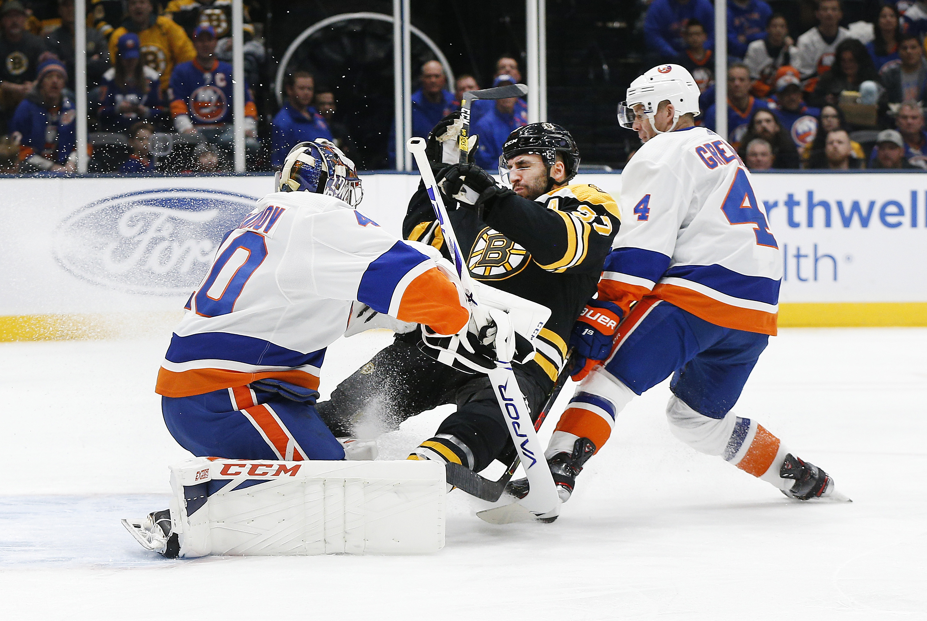 Feb 29, 2020; Uniondale, New York, USA; Boston Bruins center Patrice Bergeron (37) collides with New York Islanders goaltender Semyon Varlamov (40) during the first period at Nassau Veterans Memorial Coliseum. Mandatory Credit: Andy Marlin-USA TODAY Sports